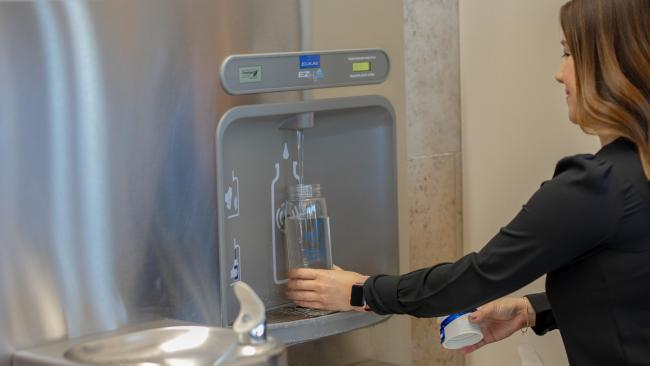 Refilling bottle at water station