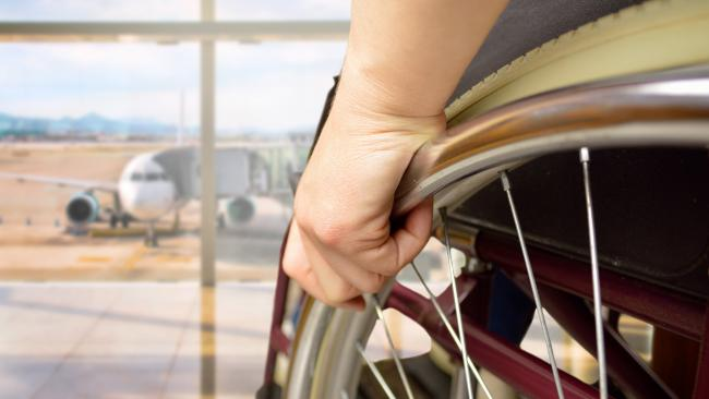 Close up of wheelchair and person looking at airplane outside on runway