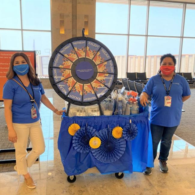 John Wayne Airport employees welcoming guests back with a freebie wheel